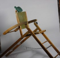 Image of Chair, Dentist's - Portable wooden dental chair used for school dental clinics. The chair has a wooden frame that collapses making it easy to carry and has a separate foot rest that is attached.  The seat of the chair is covered with a green marbled veneer as is the back rest. On the top of the back rest is a green vinyl moulded head rest. Head rest can be moved up or down.  The legs of the chair form an inverted V shape from front to back with a steel pin. The two sets of legs are joined at the front by three cross pieces (like rungs on a ladder) over which the foot rest can be attached. Top and bottom cross piece are wooden with a steel one in the centre. This has a chain that attaches to the second of the steel cross pieces at the back of the chair. Chain stops chair from collapsing too far.  The arms of the chair slants backwards and have a series of cut out shapes that allow the back of the chair and the headrest to be lowered into a variety of positions.  The separate wooden foot rest has two arms on which the green marbled veneer foot rest base sits. The ends of the arms are shaped so that they fit over the crosspieces joining the legs and there are metal lugs behind which swivel and lock the foot rest in place. The foot rest is held in a vertical position by the wooden brace at the front.