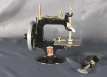 "Image of Machine, Sewing - Small black child's hand operated sewing machine with ""Peter Pan"" sticker on the oval base. Top has place for cotton reel and mechanism to work the needle up and down when being turned by the handle on the wheel on the left hand side. C shaped section open where material is threaded through under the needle.  Sticker is red oval with ""Peter Pan Model"" in blue and ""Made in Australia "" across the bottom.