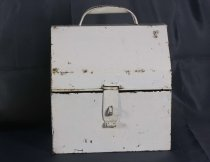Image of Tin - Tin that has been painted cream with steep lid made by Clarrie Blackwood. Rectangular tin has tab at centre front with wide slit that fits snugly over loop on bottom of tin. Tab has rounded end for ease of handling. Lid has deep, steep side with top flattened and D shaped handle attached.