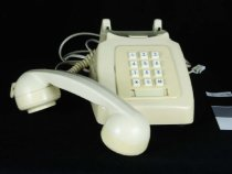 """Image of Telephone - Cream telephone that has been converted from dial to push button. Yellowed cream plastic telephone with a black base that sits on table. The face of the phone has a rectangular cream push button face but there are gaps where the round dial face has been removed when converted. Has small white buttons with the numbers """"0"""" to """"9"""" printed in black.  The handset of ear and mouth piece sits across the top of the telephone and is connected to the phone by a cream cord. There is also a cream cord at the back of the phone to connect to the outside wires with jack attachment at the end. On the base is white stamp that reads """"NZPO Wkshp T/U Overhauled/Repaired By 31. Date 12/10/79 Test By SW / / """",Four round rubber feet on the base for sitting on the table. A label is stuck along one side which has emergency and often used numbers."""