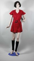 Image of Suit - Woman's two piece red wool suit  of long top and shorts handcrafted by Doris O'Brien.   Fabric: Hand woven red dyed wool (probably handspun) hand woven in chevron pattern.  Top Front: V neck line with 1.5cm binding. Centre front seam. Front centre panel extends to just below the waist. A belt with large black plastic buckle extends across front panel. Side panels extend to below hip line.  Back: Centre back seam with red invisible zip. Hook and hand made eye at the neck. Darts at the shoulder and waist. Same length as front side panel.   Sleeves: Short flared set in sleeves.  Lining: Black synthetic fully lined.  Shorts (Hot Pants!): Front: Waistband fastened at the front with two metal hooks and eyes. Fly with red zip. Darts at waist each side.  Back: Waist band has centre back join. Darts at waist each side.  Lining: Black synthetic lining, fully lined.  Label: Handmade in NZ label with wool indicated and washing instructions.