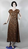 Image of Dress - Woman's long black and gold lurex dress. Fabric: Synthetic. Raised orange gold floral sprays in  lurex on black background.  Front: Bodice has a  V neckline with cross-over fronts. The right front is floating and folds to a point which is attached at the side by velcro. Under bodice is made from a black taffeta lining. There are bust and waist darts in the lining and left cross-over front. On the shoulders inside are strap keepers with domes. The long A line skirt has two smart pleats at the waist. Black metal zip in left side seam.  Back: V neckline with centre back plastic zip extending below waist. There is a black edging to the V and a black bow at the top of the zip with hook and eye. This edging and zip looks to be a later addition. Two darts come up from the waist.  The long A line skirt has a centre back seam, two small pleats at the waist and the side seams are more around to the back than the side. Two floating panels fall from the waist, either side of centre back sea. The panels are edged with a black fringe at the bottom.  Sleeves: Small cap sleeves.  Lining: Black taffeta lining in bodice  and skirt. Black organza lining for the sleeves.  Construction: Machine sewn. Raw edges turned over and machined of overlocked. Some hand hemming. Evidence of alterations - letting out darts, back zip addition.  Label: Fenn Dell Made in New Zealand