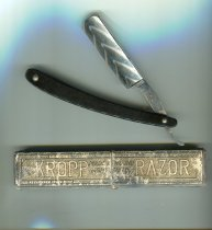 "Image of Razor, Cut Throat - Kropp cut throat razor in box. Razor has black handle and stainless steel blade which swings out. Embossed in to the blade on one side is ""Kropp"" and on the other is ""Made and ground in Sheffield England"". Tang is ridged and blade is rounded at the end.