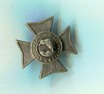 "Image of Badge, Military - 2nd South Canterbury Regiment collar badge for left hand side collar. Badge is in the shape of a Maltese cross with a kiwi in a garter. Kiwi hugs the curve of the garter and is facing left. It is made from a white metal and stands on grass. Inscribed around the kiwi, it reads ""2nd South Canterbury Battalion N.Z.I"" (New Zealand Infantry).