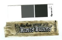 "Image of Wrapper - Small plastic wrapper for ""Peter Pan's Honey Bunny Sweetest Eater "" with instructions to ""tear here then squeeze up from the bottom"". On the other side is an image of bunny lying on the grass wearing striped overalls and eating the sweet with ""Made to be loved"" and ""Peter Pan Foods Ltd Waipukarau""."