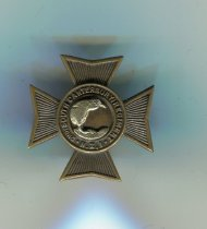 """Image of Badge, Military - 2nd South Canterbury Regiment collar badge for right hand side collar. Badge is in the shape of a Maltese cross with a kiwi in a garter. Kiwi hugs the curve of the garter and is facing right. It is made from a white metal and stands on grass. Inscribed around the kiwi, it reads """"2nd South Canterbury Battalion N.Z.I"""" (New Zealand Infantry).  On the back are two lugs which were used attach badge to collar and the pins holding the kiwi in place are visible. Also impressed into the metal is makers name """" J R Gaunt London"""""""