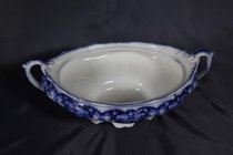 Image of Tureen - Ornate oval soup tureen with blue underglaze pattern? The tureen stands on raised base with scalloped edges. Coggle and other pattern incised or stamped in porcelain prior to glazing and small amount gold paint highlights. Tureen widen to shallow bowl shape blue floral pattern with gold highlights. Under rim is stamped pattern and scalloped rim has blue striped pattern with gold highlights. Rounded handle at each end with small thumb rest decorated with stamped pattern, blue glaze and gold highlights. Inset into inner rim is ledge for lid to rest. Lid from this tureen is missing.