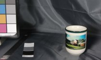 """Image of Mug - Large thick mug with colour transfer image of St Vianney's Home of Compassion. Cup has cream ground and D shaped handle. Rim is coloured with band of dark green with black at the edge.  On the base is a sticker with barcode and """"Mug Evergreen"""""""