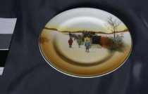 """Image of Plate, Side - Side plate ( that matches 2012/210.01) by Royal Doulton called """"Country Days"""". Plate is in pattern 12 """"Coach going up hill, attendants walking"""". It has a country scene with horses pulling a yellow coach with people (men) walking along side and has yellow brown tones as background. Hills on horizon are brown and there is a tree with no leaves in foreground. Background of brown and yellow tones with brown along horizon ( hills or trees?). More detailed image (transfer) is outlined in black pen and then coloured.  Plate is round which green on rim and indention 3cm in from rim  Seen notes for extra information"""