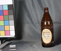 "Image of Bottle, Drink - Round squat browm glass beer bottle with paper label with ""Dominion Bitter Beer"". Also on pale brown label is ""Brewed and bottled in New Zealand by D B South Island Brewery Ltd Timaru 745 ml"""