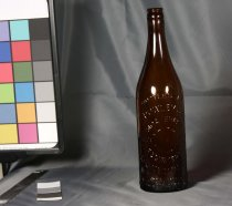 "Image of Bottle, Drink - Tall brown glass beer bottle with embossed on the bottle ""Bottled by R Powley and Co Moa Brand  Dunedin""  Label information embossed on front, bottle refund information on lower back"