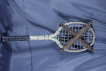 "Image of Racket, Tennis - Wooden tennis racket with racket protector. Racket is made with a pale wood and is painted in places with pale yellow paint. Sticker on racket reads ""Slazenger choice of the champions"" and ""Matchpoint"". Sticker on both sides of handle reads ""Precision handstrung by Otago Sports Depot Ltd Dunedin"". Rubber grip on handle.