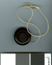 """Image of Yo-yo - Small round dark brown Bakelite yo-yo. One side has """"Howdo"""" embossed in the centre. Other side has small logo in the centre with """"NZPP"""" embossed. String attached to groove down the centre."""