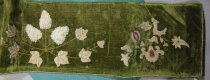 Image of Manteldrape - Olive green beaded velvet manteldrape.  In the centre of the drape is a large spray of grapes and leaves. The three bunches of grapes are made with large white and some pale gold pearl beads stitched on a raised ground. Many beads are missing. The leaves are sewn with small white glass beads and the veins, tendrils and stems are made with small gold glass beads.  At either end of the drape is a large floral spray using white, gold and red small glass beads for the flowers, seedhead and leaves. The spray on the left end has beads missing. Around the top and side edges there is a twisted cord of white and gold beads.   The drape is stiffened with cardboard on the back (the beading stitches go through the cardboard) and then backed with green cotton fabric.