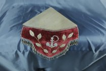 Image of Manteldrape - Two red velvet beaded corner shelf drapes. (One still attached to wooden frame). The drape is almost an inverted triangle in shape  In the centre of the drape is an anchor in white glass beads. One has a pearl bead at the top, the other it is missing. Around the anchor is a spray of leaves. Along the top and sides of the drape is a twisted cord of white and gold beads. The lower edge has a fringe of beads.  The drape is stiffened with thin cardboard and the beading stitched come through it.