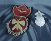 Image of Pocket, Wall - Red velvet beaded wall pocket.  Pocket has a bee worked in white and gold small glass beads. The is a small beaded flower at the top of the pocket. A twisted cord of beads edges the top and a fringe of beads falls from the lower edge.  The pocket was probably made for the small white and gold porcelain dish featuring Christ on the cross. This would have held holy water.  Pocket is stiffened with cardboard and backed with red cotton.