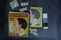 "Image of Puzzle - Small cardboard box with ""Funni-face Jigsaw Game for the young and the not so young"" in yellow on red band. Has a man's face on cover with red and yellow. Small logo for ""Mere for merriment""