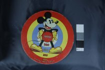 """Image of Target, Gallery - Round thick cardboard target with Mickey Mouse in the centre. Mickey is holding a centrally placed red circle with the number 1000 on it. Radiating out from this circle are others starting with white with 500, blue with 300 and yellow with 200 and at the edge a red circle with 100 on it.  At the bottom is """"Mickey Mouse target licensee for British Empire excluding Canada The Chad Valley Co Ltd, Harbourne, England by arrangement with Walt Disney Mickey Mouse Ltd.""""  At the back is small square wooden block to mount target. Not sure what was used to fire at the target but most likely suction dart guns. There are round marks on the target that also suggest this."""
