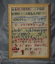 Image of Embroidery - A framed embroidery created by Johanna Burnett, July 1877, depicting the Alphabet, numbers, symbols and pattern in various bright colours.