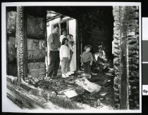 Image of The Harvey Family view the remains of their burnt out house - Timaru Herald Photographs, Personalities Collection