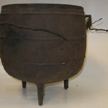 Image of Three-legged Iron Kettle - Three-legged iron kettle belonging to John G. Morrison, Jr. (1873-1964). Includes a wire handle, but wire handle is broken.