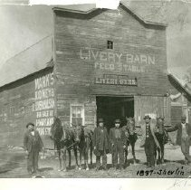 "Image of Shevlin Livery Barn Feed Stable - Five men and a woman or child posing with horses next to the Livery Barn Feed Stable, Shevlin, 1897. Writing on photo reads ""Now a Garage.""