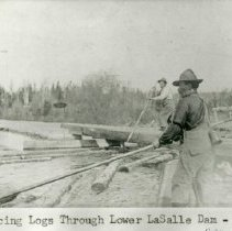 Image of Sluicing logs through Lower LaSalle Dam - 2 loggers Sluicing logs through Lower LaSalle Dam, 1909. Wilson Minor in foreground, father of Jim Minor.