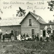 Image of First Fourth of July celebration at the George Gunderson Store - First Fourth of July celebration, George Gunderson Store, Inez township,1904 About 25 people and 3 horses in front of the store
