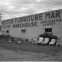 "Image of Reuter Furniture Mart - Reuter Furniture Mart, 104-108 3rd Street. Owner was Virgil Reuter. June 1960. Image shows outside of the building with lawn chairs in front. Building also says ""New & Used Furniture, Warehouse, Appliances, Carpet.""  This warehouse was at 528 Midway Drive in 1960."