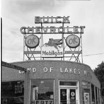 "Image of Land of Lakes Motors - Land of Lakes Motors, Hertz Rentals, Bemidji, Third Street and Irvine Avenue, June 1960. Sign on top of building reads ""Buick Chevrolet, Mobilgas, used cars, used trucks."""