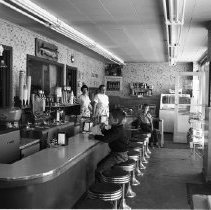 Image of Red Cap Dairy - Red Cap Dairy, 207 2nd St., Bemidji. Owner, Eldon Darst. People in photograph Millie ? behind counter; Peter Nordquist eating ice cream cone in foreground; Paul Nordquist further back on stool. June 1960.