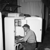 Image of Refrigerator Repairman - Refrigerators and repairman, possibly Bemidji Coop Association, with Marshall Schroeder in the picture. June 1960.