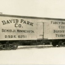 Image of David Park Company Train Car - Postcard of a David Park Company railroad box car. Train car is pictured by itself on tracks. Writing on the side of it reads: Dave Park Co., Bemidji, Minnesota, D.S.D.X 6251, Fancy Northern Eggs, Butter, Turkeys. Dates to at least 1938, likely to 1929 or 1930.