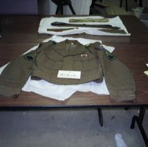 "Image of 00.10.01 - Korean War Uniform Jacket. Two front breast pockets.  Pin above left front pocket:  black, red, and white.  Patch on each sleeve and shoulder.  Patch on left sleeve reads ""Seven Steps to Hell"" and displays a gold pyramid.  Shoulder patches read:  ""Undaunted, unconquered, unexcelled."""