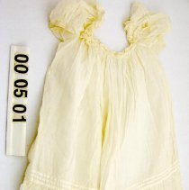 Image of 00.50.01 - Child's white cotton dress with puffy short sleeves.  Square neckline with lace and ruffles, tucks around bottom.