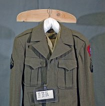 "Image of 01.02.01 a,b - World War II Army jacket of Eunice A. Arey. Two front breast pockets, five hidden buttons down front, collar. Blue ticket ""987"" sewn into waist line."
