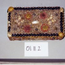 Image of 01.11.02 - Shell Art Box.  The shells are painted and arranged to form patters.  The borders are circular snail shells painted black, the sides have an additional border painted yellow.  Small shells painted yellow create the background for red and yellow flowers f