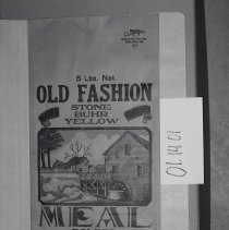 "Image of 01.14.01 - Mill bag from Plains Mill in Timberville.  ""5 lbs. Net.   Old fashion water ground Stone Buhr Yellow Meal, bolted.  Manufactured by Plains Milling Co., Timberville, VA  Phone 22-F-22"".  Image of side of mill beside stream in red, yellow, green, and blue"