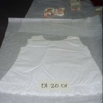 Image of 00.20.01 - Childs cotton dress. Bustle fullness below waist in back. Ruffles on bottom. Back longer than front.