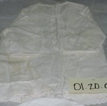 """Image of 01.20.02 - Baby's white gown. Lace along neckline and edge of 3/4 length sleeves.  Two vertical lines of decorated stitching line front.  Flwoers are embroidered laong himline; 2 1/2"""" ruffle or hem is along bottom.  Back closure with three small buttons."""