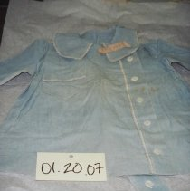 Image of 01.20.07 - Child's:  Blue dress, collar with white edging.  White edging also along right breast pocket.  Five buttons down center.  Belt attached at back.  One belt loop on each side at seam.  Long sleeves slightly tapered.