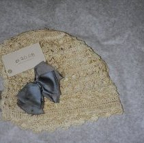 Image of 01.20.08 - Child's white crocheted cap with blue bow.  Design of lines of scalloped shells.