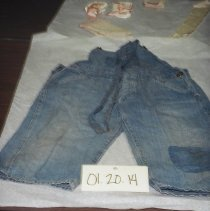 Image of 01.20.14 - Children's jeans overalls.  Patch on left leg.  Buttons which connect straps have leaf design. Two back pockets.  Worn.