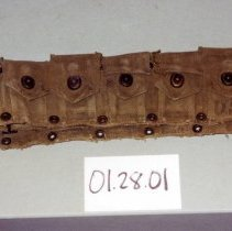 Image of 01.28.01 - Cartridge belt.  Ten pockets, five on each side of buckle.  Each pocket has clasp.  Stamp on back side is illegible.