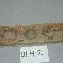 "Image of 01.04.02 - Wooden Maple Sugar mold.  Two pieces of wood nailed together (23 nails on bottom, 2 on top).  Bottom piece incised to create design on top of molded sugar.  Top piece is hole with etchings on the side.  The molds are 1 1/8"" deep.  Molds are: Cross (2 3/4"