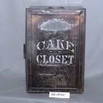 "Image of 00.15.05 - Black Tin Box with silver letters  ""Cake Closet"" ; two shelves inside, hinged door opens with hasp.  Box about 2 feet high and about 1 foot wide."