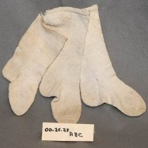 Image of 00.25.28 a,b,c - Three white cotton hand knit child's socks tied together with cotton thread. The larger pair has a ribbed top and the smaller one has a flat ribbed top.