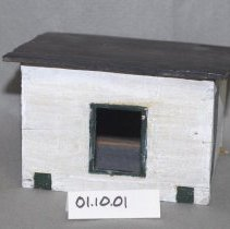 "Image of 01.10.01 - Model chicken house.  Two windows (2 x 2 1/2"") on front and side.  Door on side.  House painted white, with green trim on windows and door.  Roof is painted black.  Two sticks on bottom represent skids.  These allowed the houses to be moved to avoid dise"