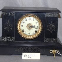 "Image of 01.12.01 a,b - A.  Black marble Ansonia mantel clock.  Flower/leaf decoration on sides and bottom of front.  Marble on four sides on front B. Key to wind the clock. (2""x 2"").  Fits into two holes on face of clock."