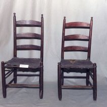 "Image of 01.15.03 a,b - Two wooden chairs.  The seats are made of tanned animal skin.  Three horizontal boards create the back.  Two ""sticks"" on each bottom side for support, and one on front and back.  Seat is animal hide (likely deer or beef) attached by woven strips of hide."